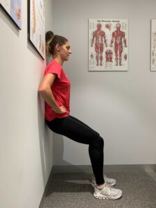 Woman performs a wall sit exercise with back against wall and knees bent