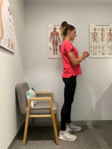 Woman stands upright after completing a sit-to-stand exercise